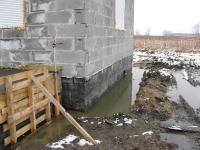 Zalanie powierzchni działki i wykopu pod drenaż wodami opadowymi - efekt braku rur spustowych z dachu budynku